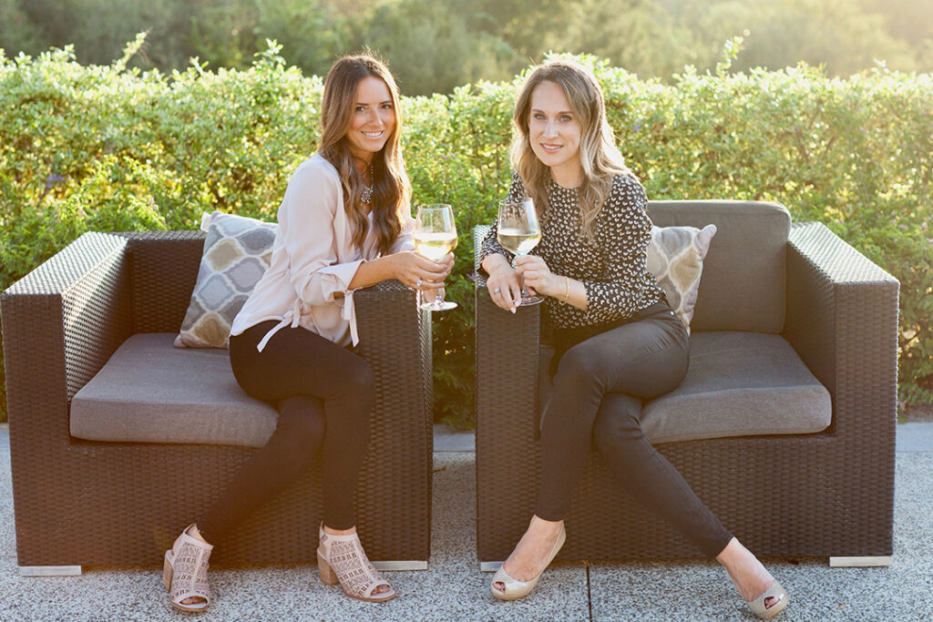 business women posing with wine glasses