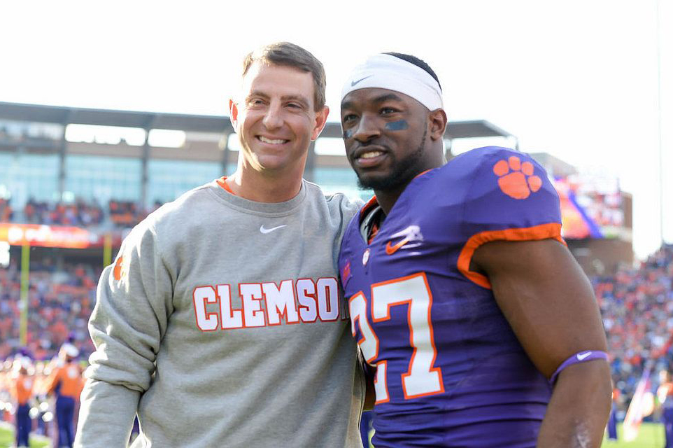football player posing with coach clemson university tigers dabo swinney