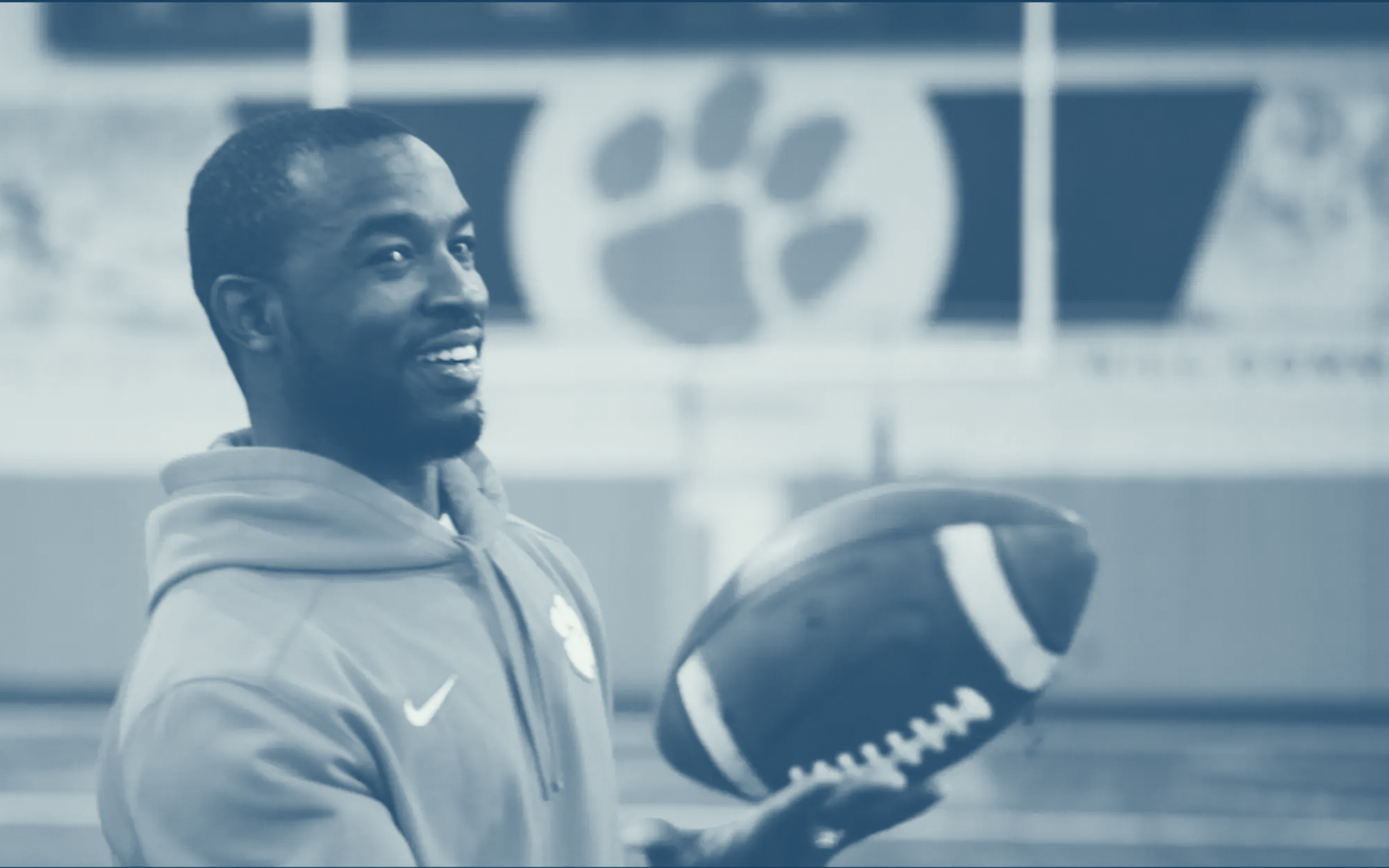 man smiling holding football clemson university tigers